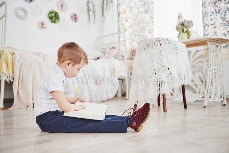 O rapaz pequeno bonito está indo educar pela primeira vez Criança com saco e livro de escola A criança faz uma pasta, sala de cri foto de stock royalty free