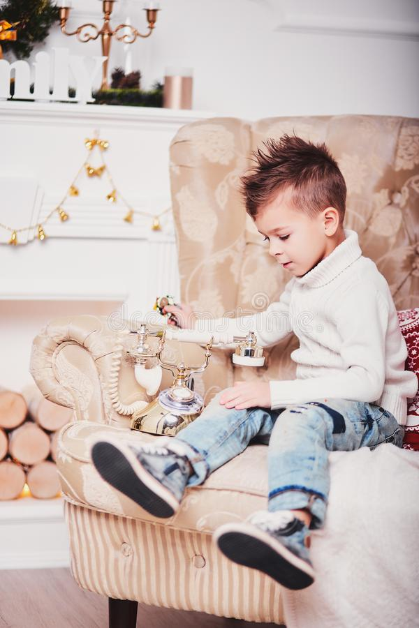 O rapaz pequeno bonito está sentando-se no sofá e está olhando-se um telefone dourado velho Um indivíduo com um corte de cabelo I imagem de stock