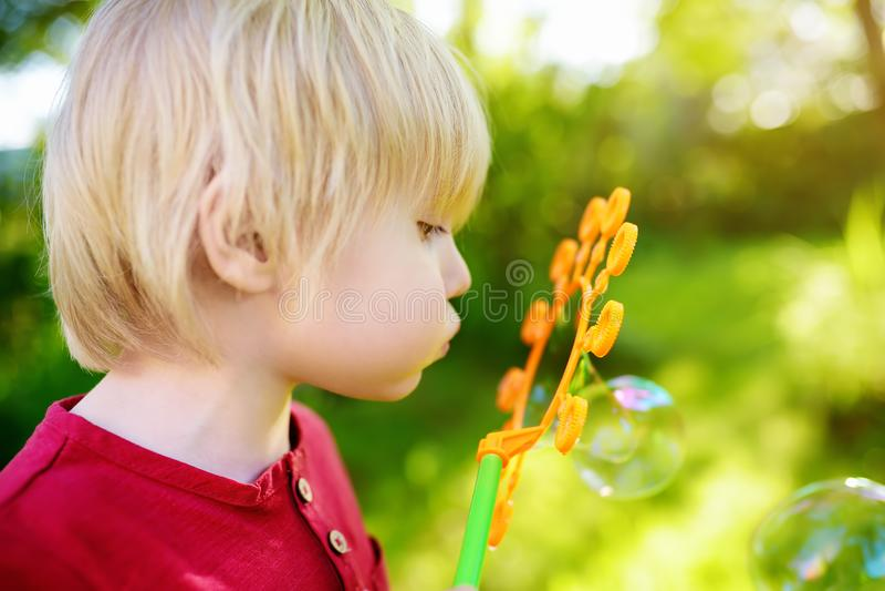 O rapaz pequeno bonito est? jogando com as bolhas grandes ao ar livre A criança está fundindo bolhas grandes e pequenas simultane imagens de stock royalty free