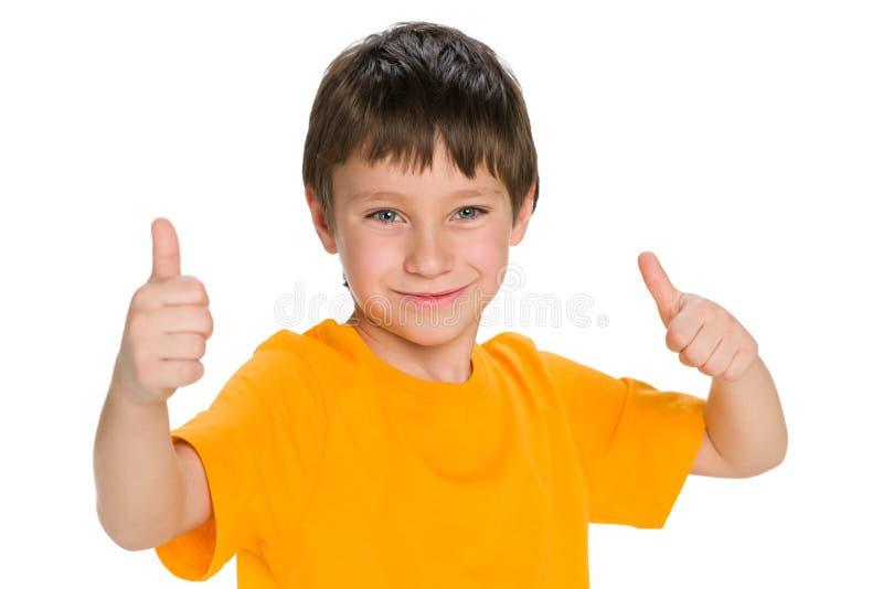 O rapaz pequeno bonito mantém seus polegares imagem de stock royalty free