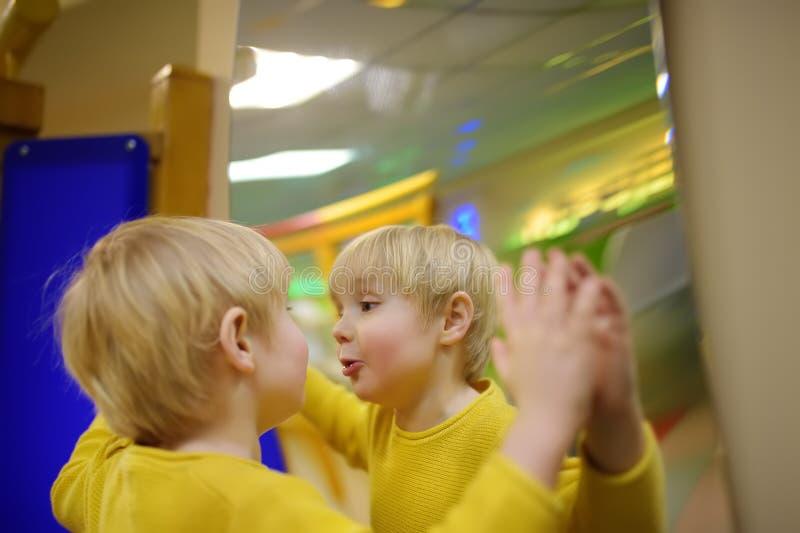 O rapaz pequeno bonito olha em distorcer o espelho no playcenter imagens de stock royalty free