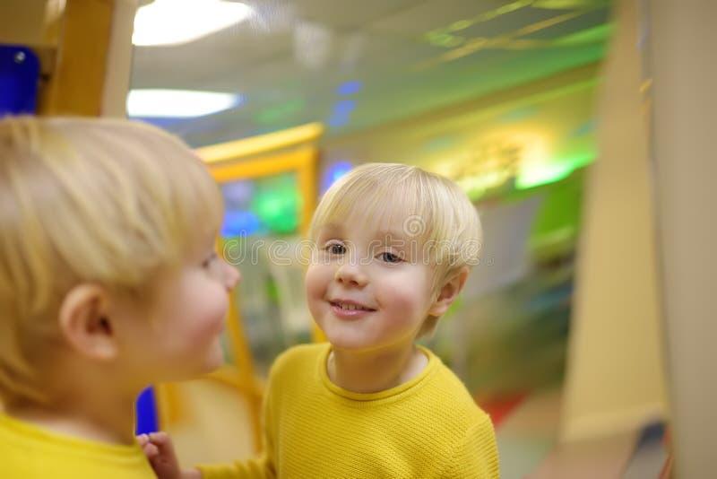 O rapaz pequeno bonito olha em distorcer o espelho no playcenter imagens de stock