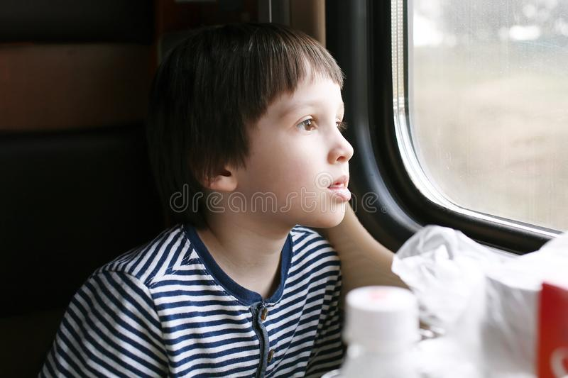 O rapaz pequeno bonito olha fora da janela no trem imagens de stock