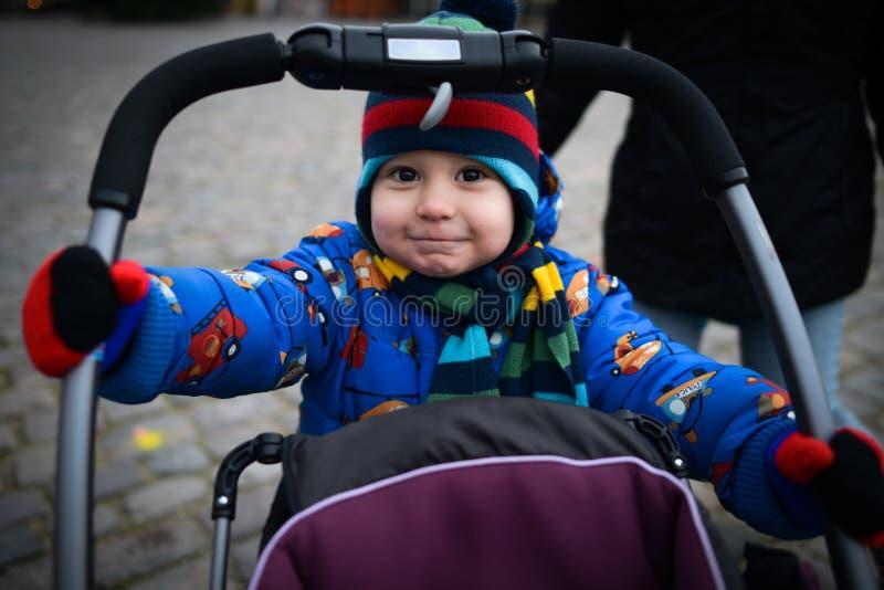 O rapaz pequeno bonito rola o carrinho de criança de bebê na rua fotografia de stock royalty free