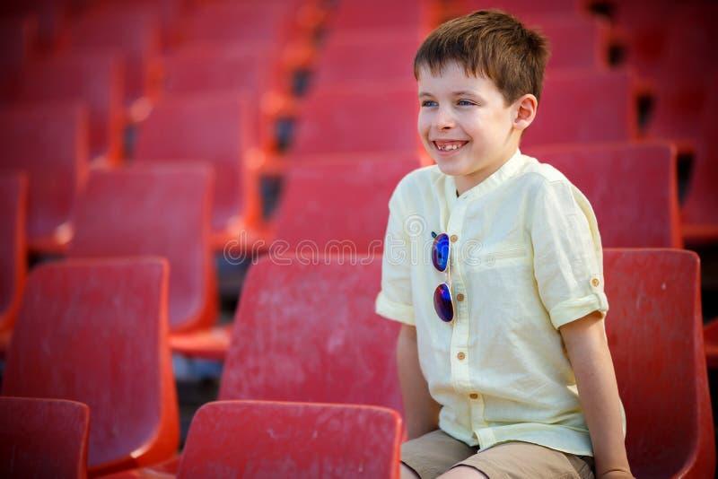 O rapaz pequeno bonito senta-se em uma tribuna foto de stock royalty free