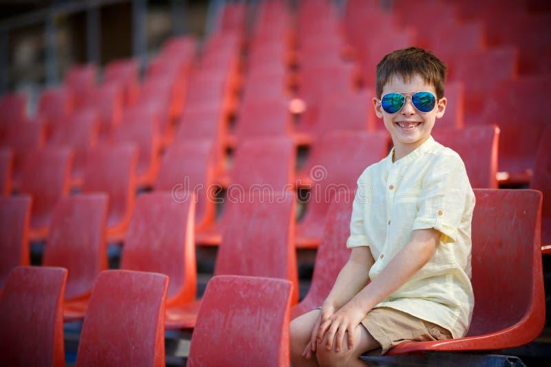 O rapaz pequeno bonito senta-se em uma tribuna foto de stock
