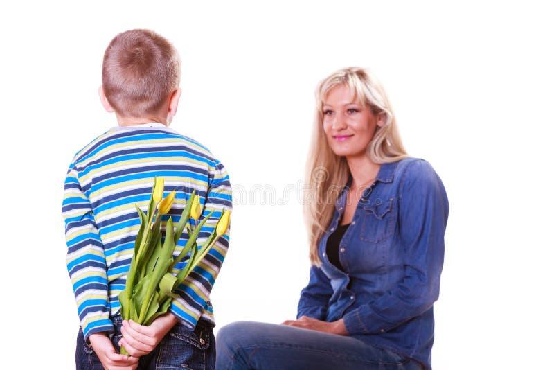 O rapaz pequeno com as flores da posse da mãe atrás suporta fotografia de stock royalty free
