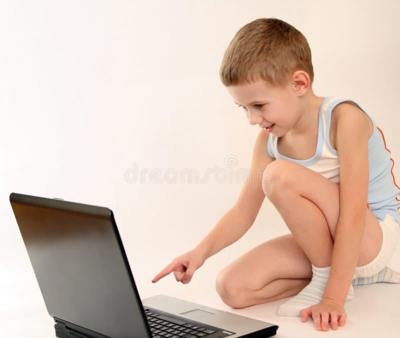 O rapaz pequeno com portátil imagens de stock royalty free