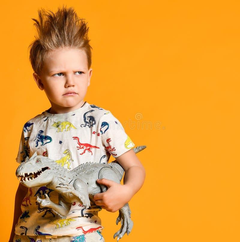 O rapaz pequeno com um cabelo engraçado, bagunçado guarda o dinossauro plástico do brinquedo como um retrato fotos de stock
