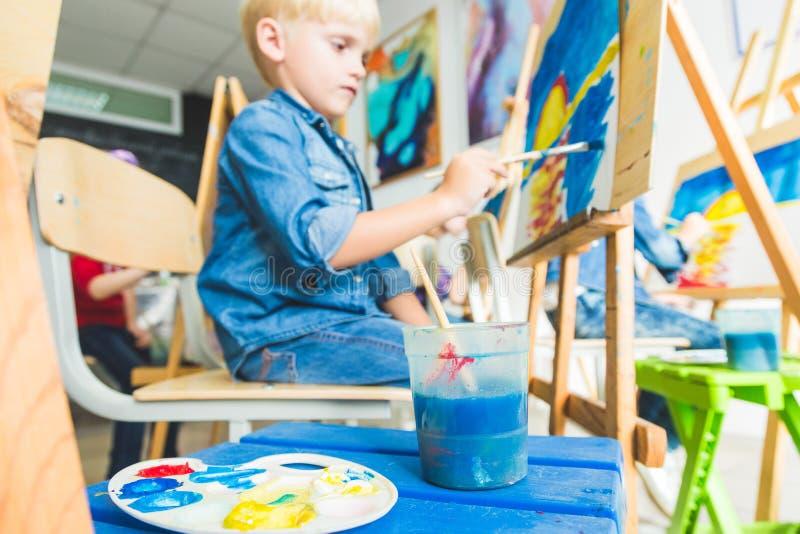 O rapaz pequeno com um professor no grupo de estudante pré-escolar sentou o desenho uma imagem Pintura no maelbert, paleta e imagem de stock royalty free