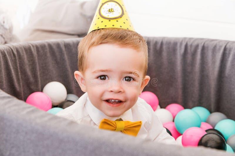 O rapaz pequeno comemora o aniversário em uma associação com bolas plásticas fotos de stock