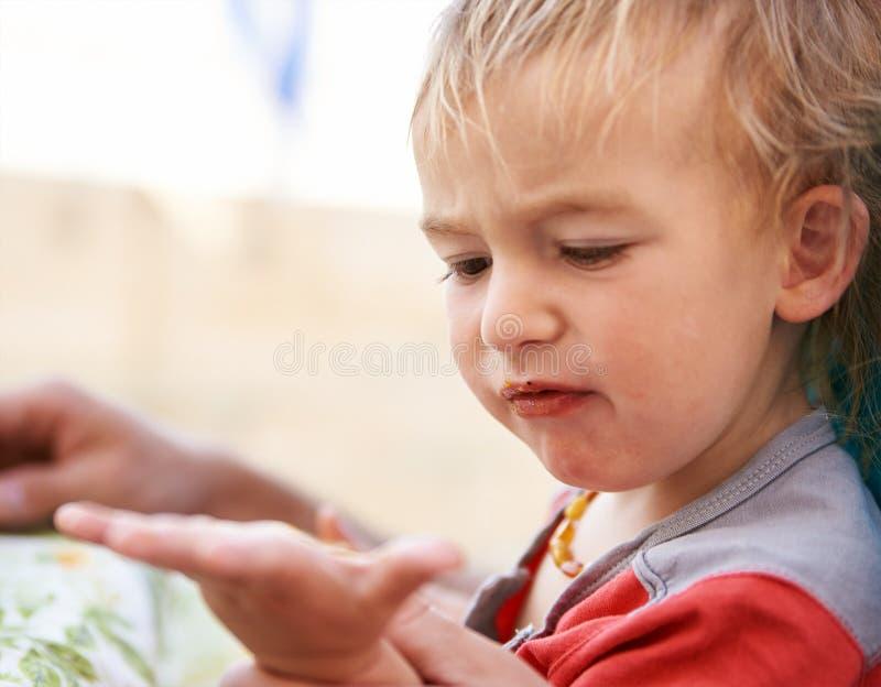 O rapaz pequeno da criança come imagem de stock