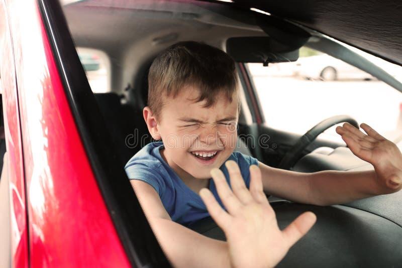 O rapaz pequeno de grito fechou-se dentro do carro imagem de stock