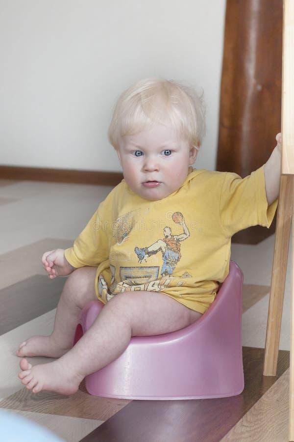 O rapaz pequeno de 8 meses senta-se em um potenciômetro fotografia de stock