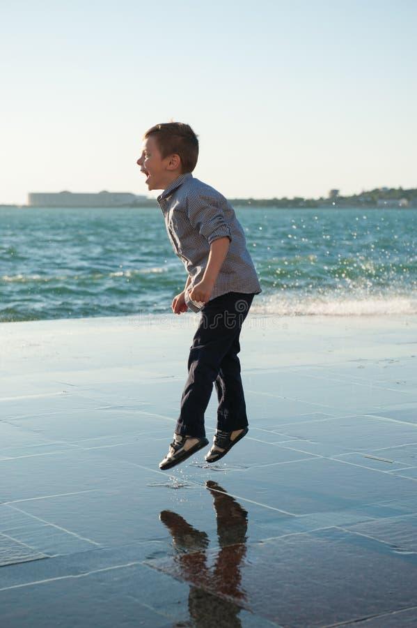 O rapaz pequeno de salto de riso no fundo de um mar ataca imagem de stock royalty free