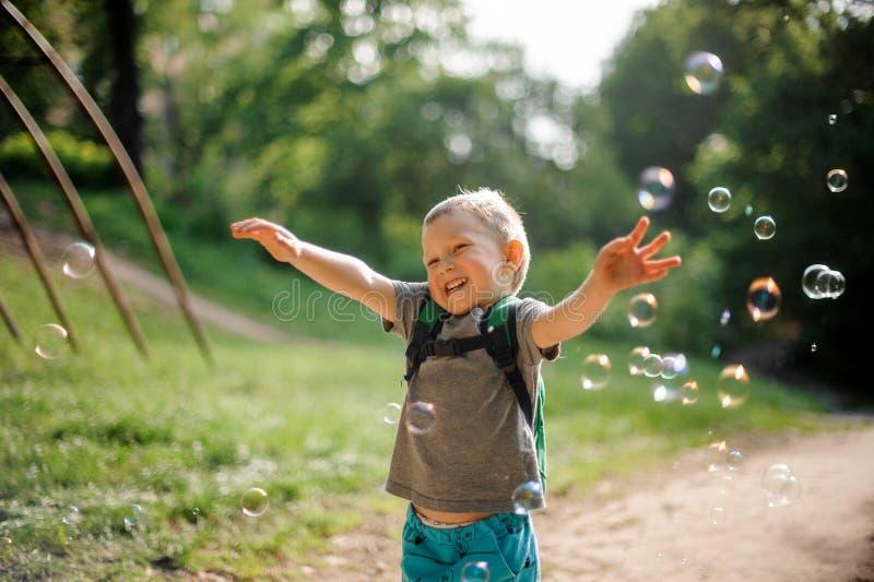 O rapaz pequeno de sorriso com bolhas de sabão no verão estaciona no dia ensolarado imagem de stock