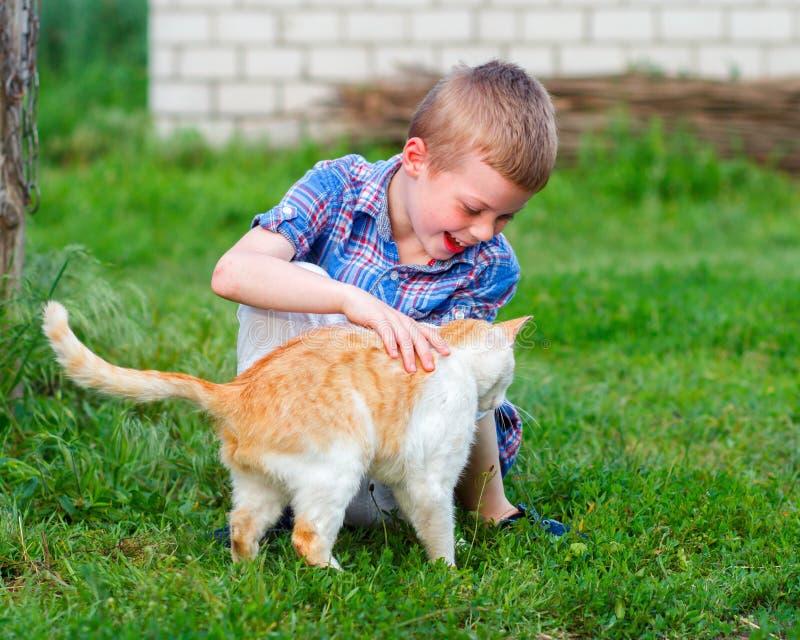 O rapaz pequeno de sorriso na camisa quadriculado joga com um gato vermelho foto de stock