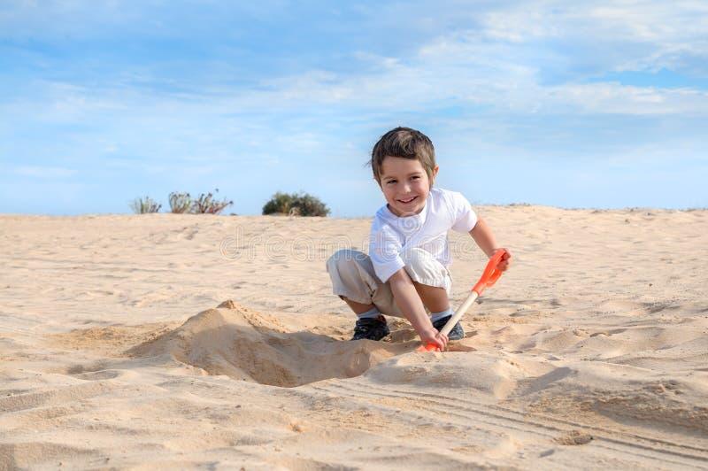 O rapaz pequeno de sorriso no t-shirt branco escava a areia em uma praia fotos de stock royalty free