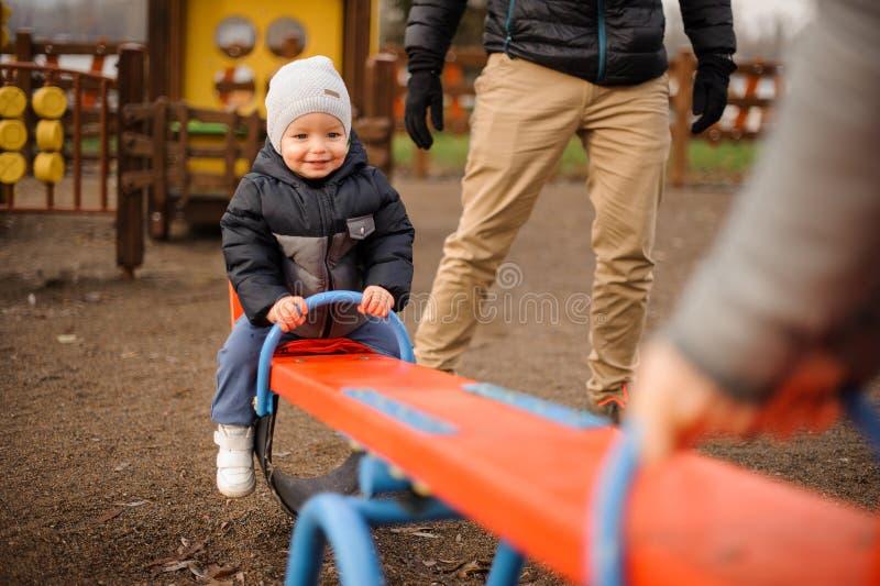 O rapaz pequeno de sorriso vestiu-se na equitação morna do revestimento e do chapéu no imagem de stock