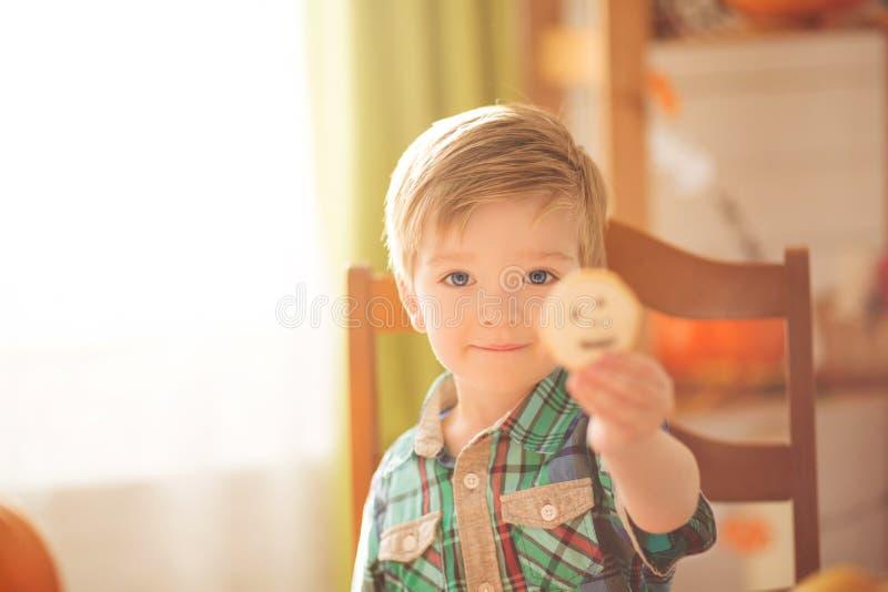 O rapaz pequeno decorou cookies para Dia das Bruxas e mostra cookies na câmera Menino bonito da criança que prepara-se para uma c imagem de stock royalty free