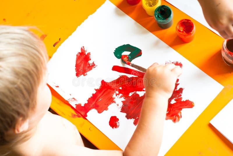 O rapaz pequeno desenha imagem de stock