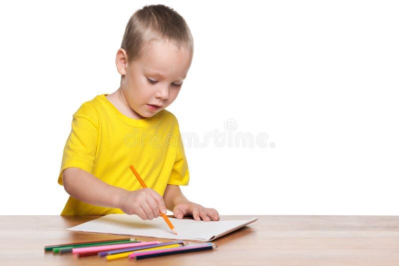O rapaz pequeno desenha na mesa fotografia de stock royalty free