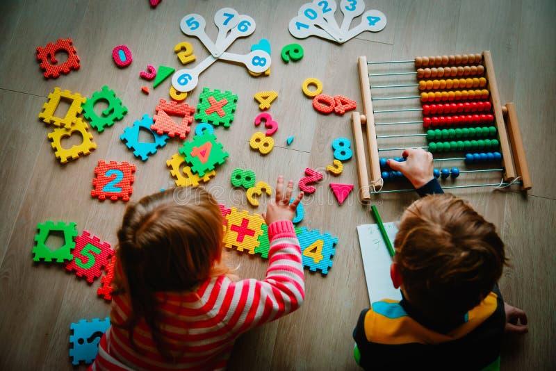 O rapaz pequeno e a menina aprendem calcular números fotografia de stock royalty free
