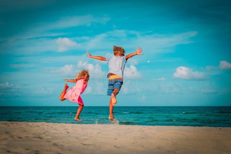 O rapaz pequeno e a menina felizes apreciam o salto do jogo na praia foto de stock