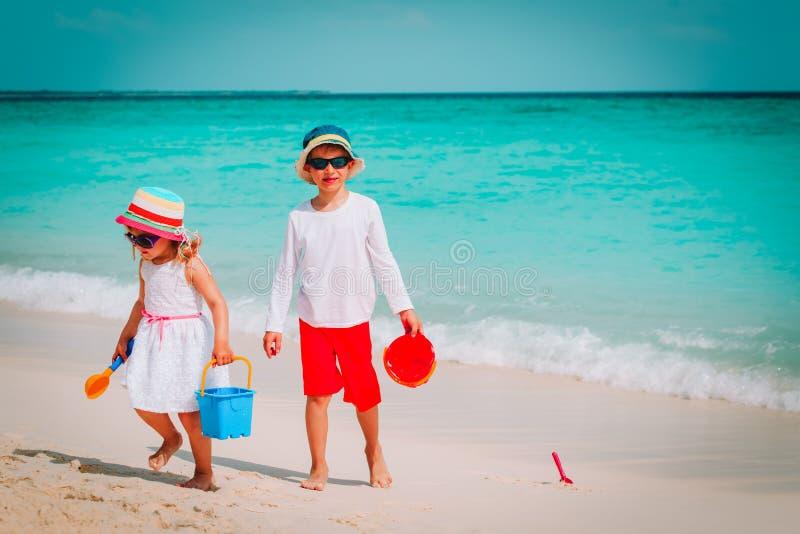 O rapaz pequeno e a menina felizes jogam com a areia na praia imagem de stock royalty free