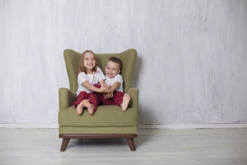 O rapaz pequeno e a menina são irmão e a irmã senta-se em uma cadeira verde imagens de stock royalty free