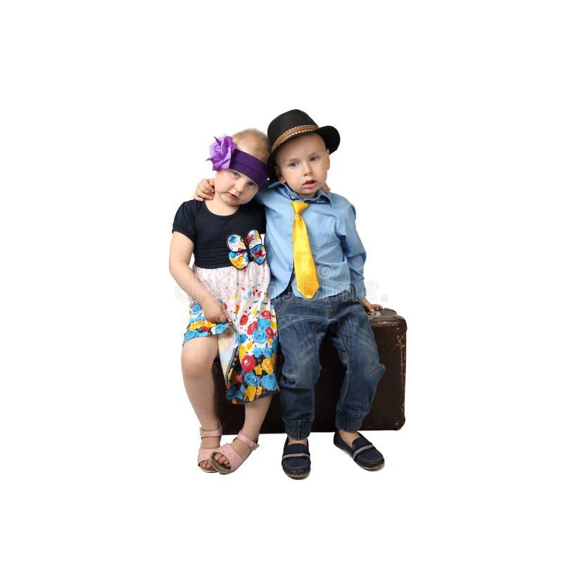 O rapaz pequeno e a menina sentam-se na mala de viagem do vintage imagem de stock