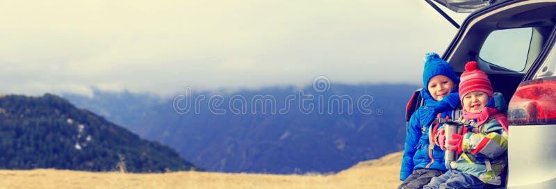 O rapaz pequeno e a menina viajam pelo carro nas montanhas, panorama imagens de stock royalty free