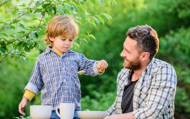 O rapaz pequeno e o paizinho comem Nutri??o org?nica Conceito saud?vel da nutri??o H?bitos da nutri??o A fam?lia aprecia a refei? imagem de stock