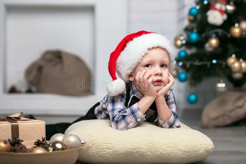 O rapaz pequeno em decorações do Natal espera um milagre foto de stock