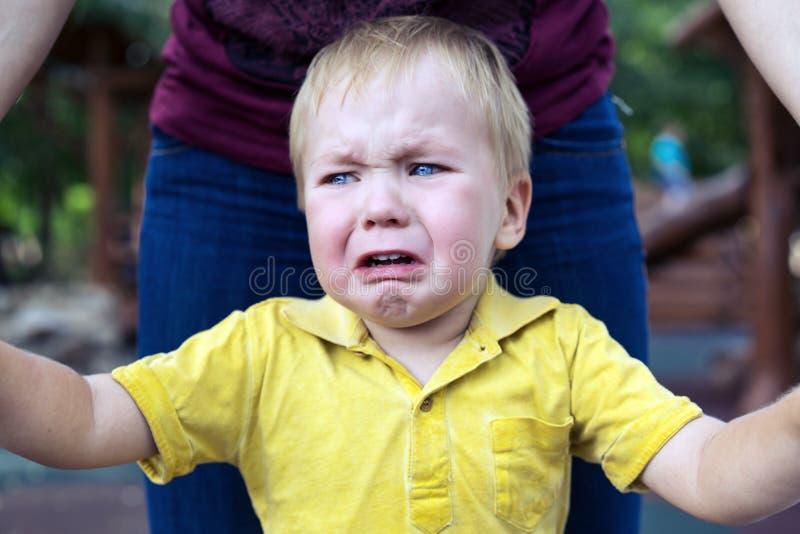 O rapaz pequeno em um t-shirt amarelo ? virado mal e gritar Rasgos em seu mordente foto de stock royalty free
