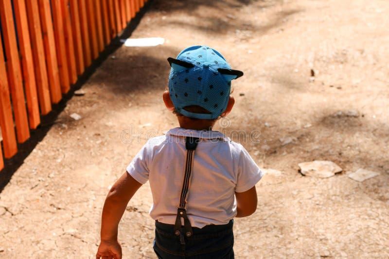 O rapaz pequeno em um tampão engraçado em algum lugar vai imagem de stock