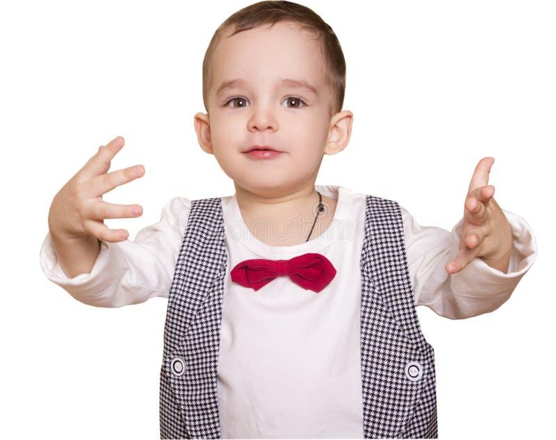 O rapaz pequeno em um terno e em um laço quadriculado joga suas mãos fotos de stock royalty free