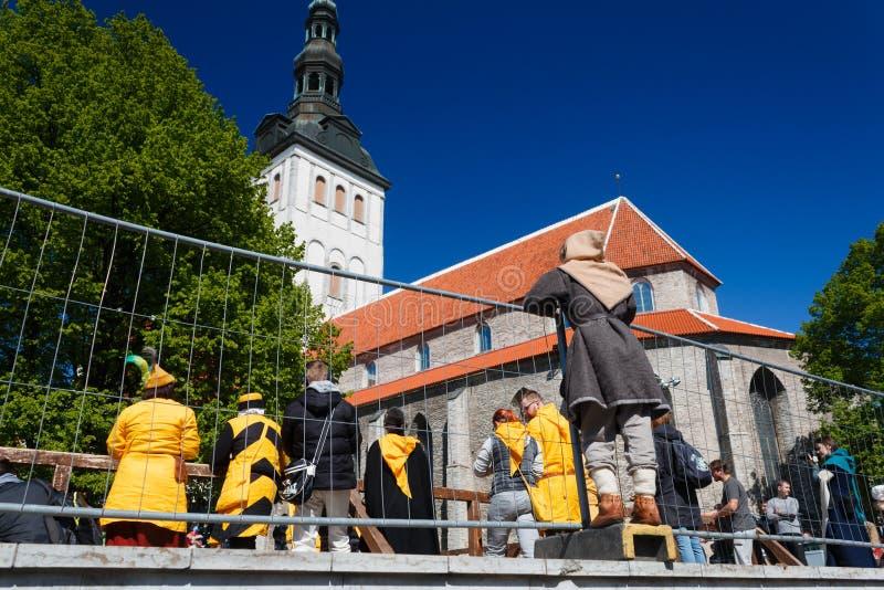 O rapaz pequeno em um vestido medieval-formado olha a luta do ` s do cavaleiro em Tallinn fotos de stock