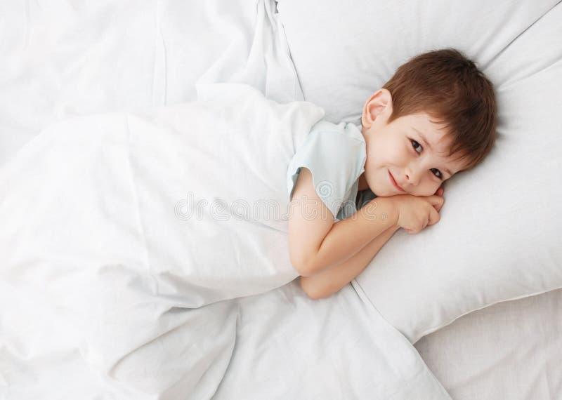O rapaz pequeno em uma cama foto de stock
