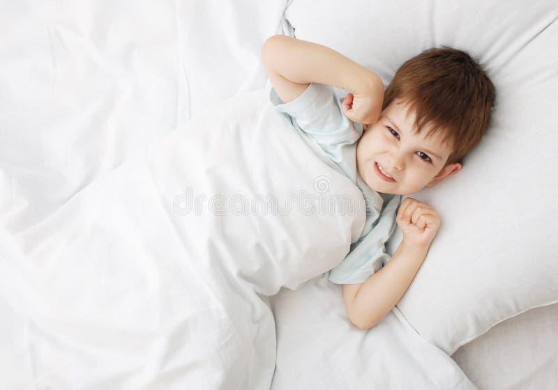 O rapaz pequeno em uma cama fotografia de stock