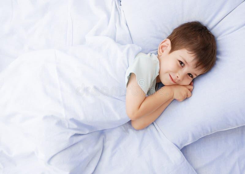 O rapaz pequeno em uma cama imagem de stock royalty free