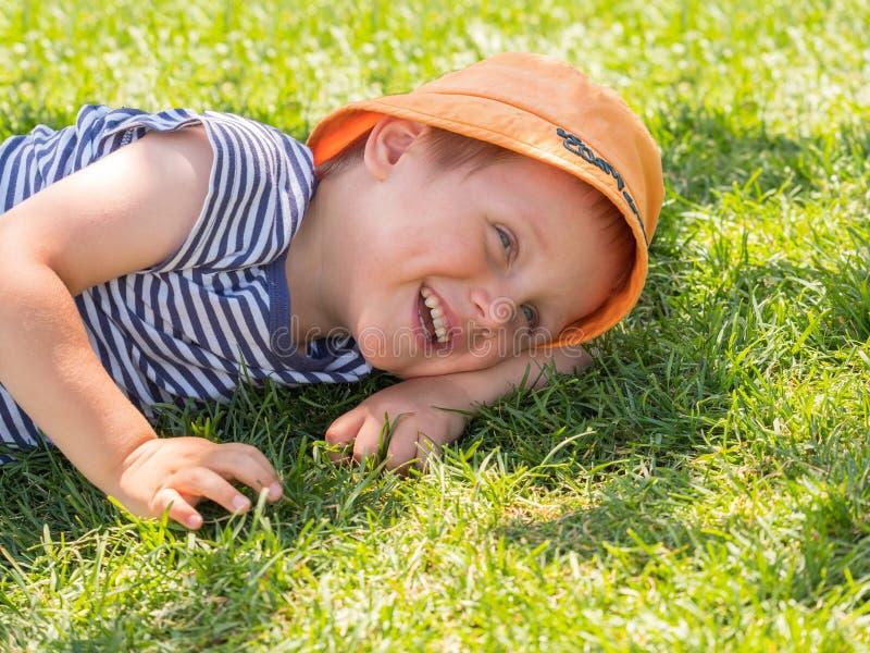 O rapaz pequeno encontra-se em um gramado verde foto de stock