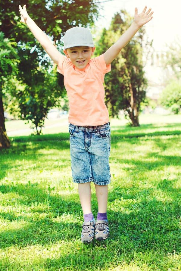 O rapaz pequeno engraçado salta fora Conceito feliz e saudável da infância Menino bonito que joga no parque do verão A criança fe fotografia de stock royalty free