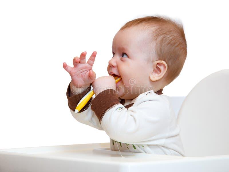 O rapaz pequeno engraçado tem o jantar foto de stock royalty free