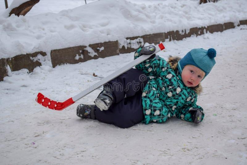 O rapaz pequeno era cansado de jogar o hóquei e ia descansar na neve com uma vara no inverno em um parque fotografia de stock royalty free