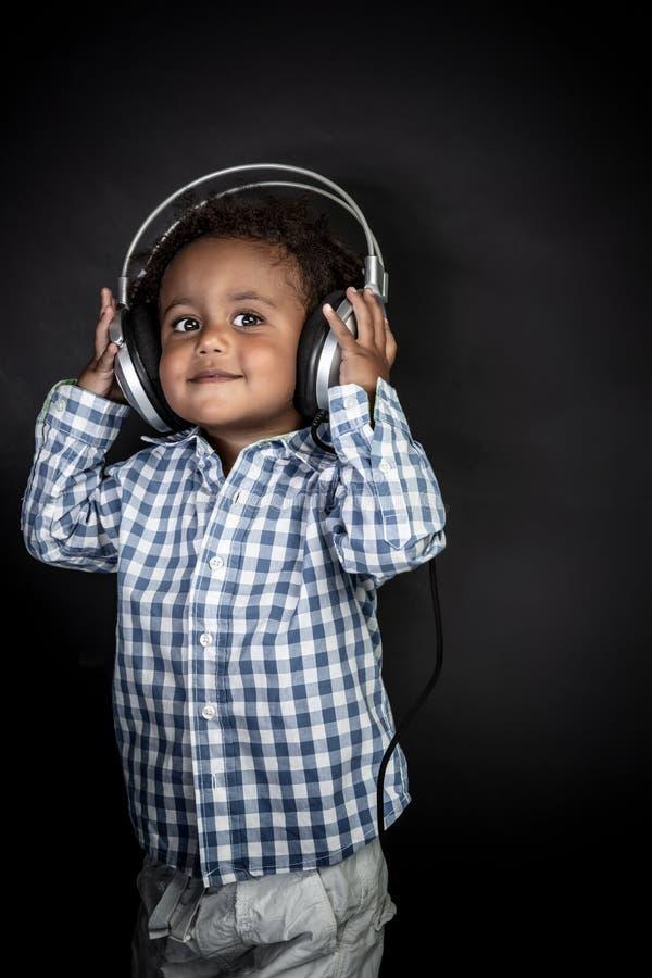 O rapaz pequeno escuta música fotografia de stock