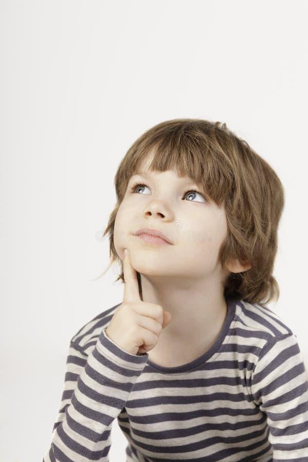 O rapaz pequeno esperto com pensamento sério enfrenta o fundo branco imagem de stock