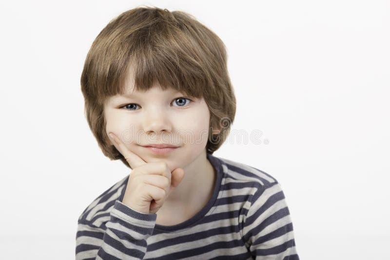 O rapaz pequeno esperto com pensamento sério enfrenta o fundo branco fotos de stock
