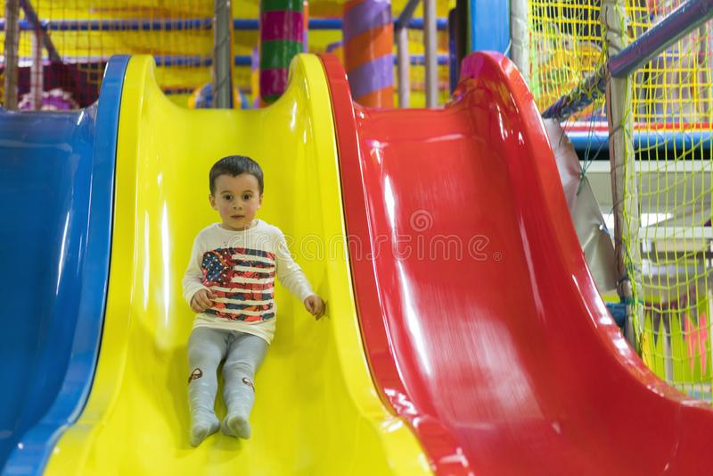 O rapaz pequeno está indo abaixo de uma corrediça no campo de jogos Está rindo e está tendo o divertimento no gym de selva Equita imagem de stock royalty free