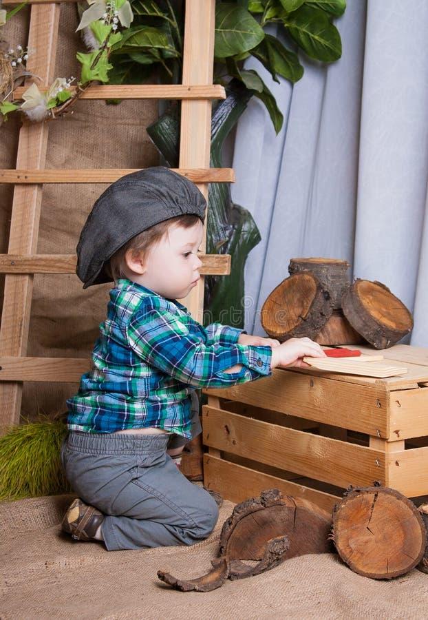 O rapaz pequeno está jogando com as ferramentas de um carpinteiro imagens de stock royalty free